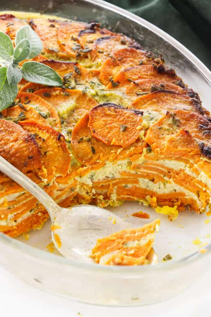 Scalloped sweet potato casserole in a casserole dish showing the layers of potato and cheese.