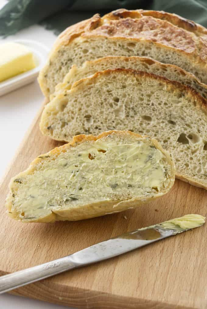 No-knead rosemary bread sliced and slathered in butter.