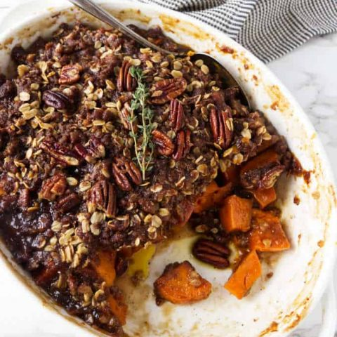 Sweet potato casserole in a white dish with pecan streusel on top.