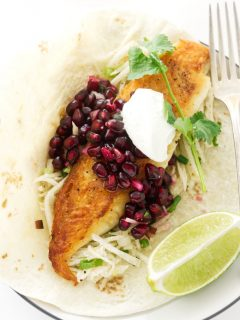 Fish taco with pomegranate salsa, jicama slaw and a lime wedge
