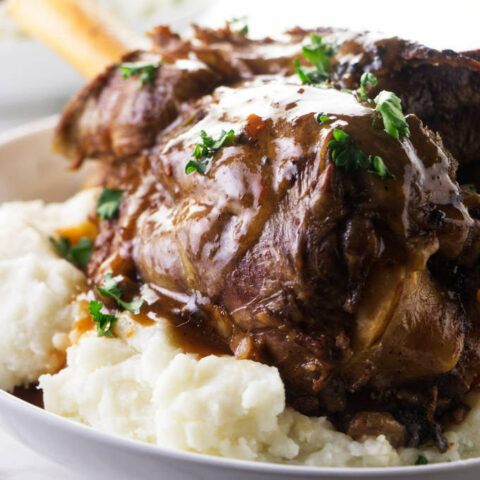 A lamb shank on a bed of mashed potatoes with gravy on top.