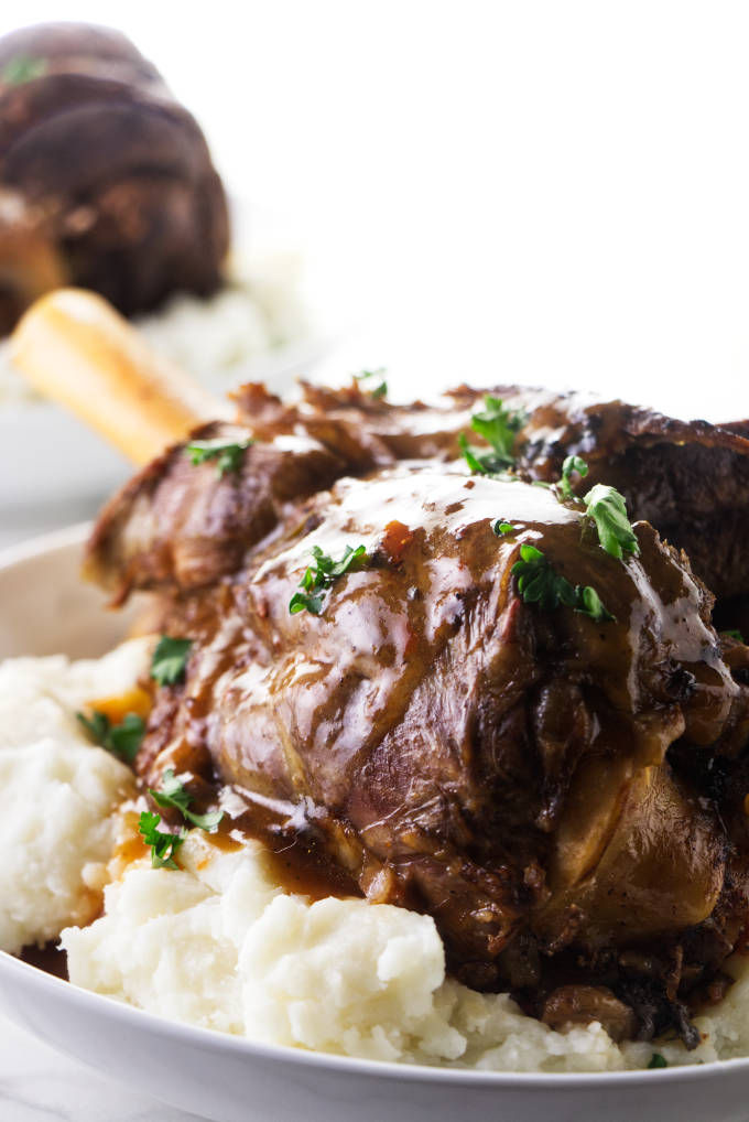 Instant Pot lamb shank on a bed of mashed potatoes.