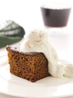 A serving of stout gingerbread cake with whipped cream