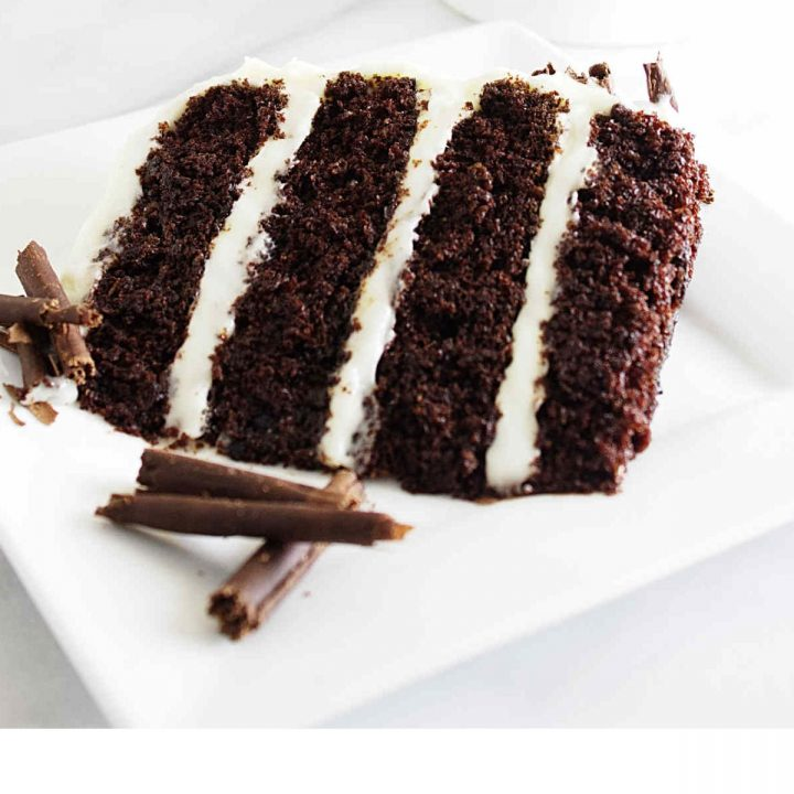 A slice of chocolate cake with cream cheese frosting on a dessert plate.