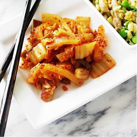 A plate of kimchi with chopsticks and fried rice