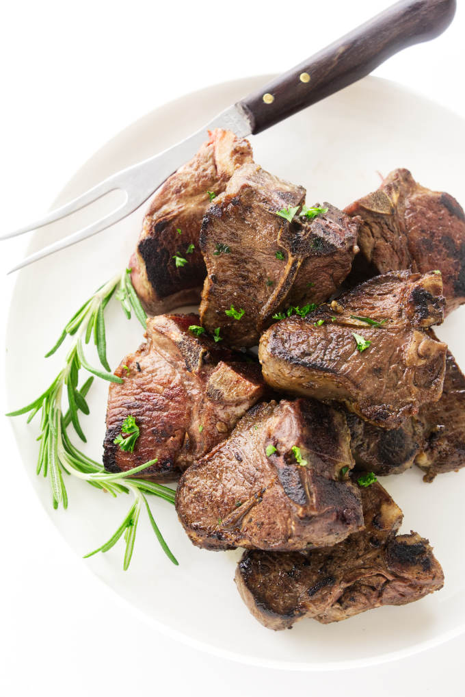 Overhead view of lamb chops on a plate with serving fork
