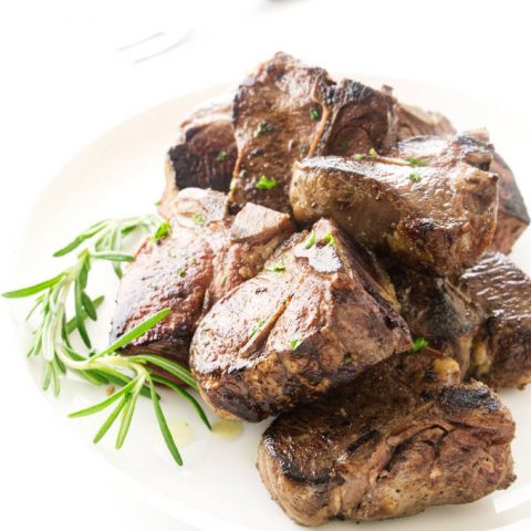 View of pan fried lamb chops on a plate with fresh rosemary garnish. Serving fork in background