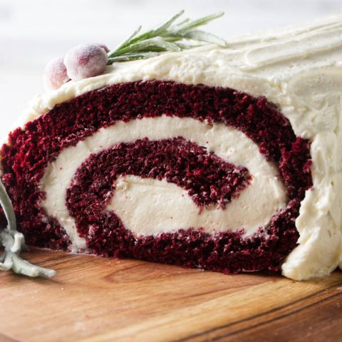 Red velvet cake roll showing the end of the roll with the swirl of cake and ermine frosting filling.