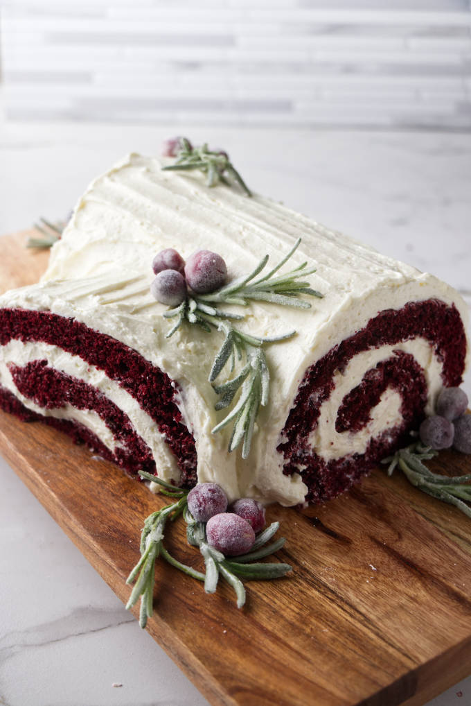 Red velvet cake roll with a part of the roll on the side of the cake to look like a branch attached to a log.