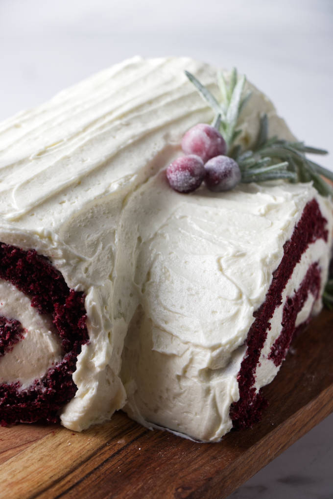 Close up of a red velvet cake roll covered in ermine frosting.