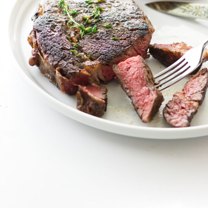 A ribeye steak sliced on a plate after being cooked in the oven.