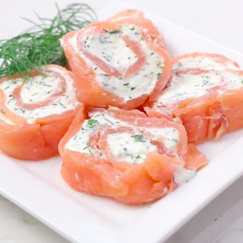 Smoked salmon pinwheels on a plate with fresh dill.