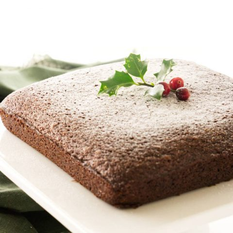 Stout gingerbread cake on pedestal, dusting of sugar 'snow' and holly/berry decorations