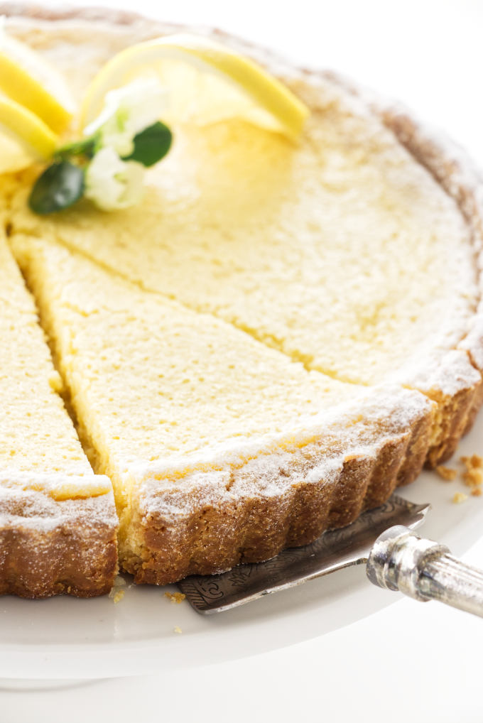 Close up view of a cut slice of lemon tart being served