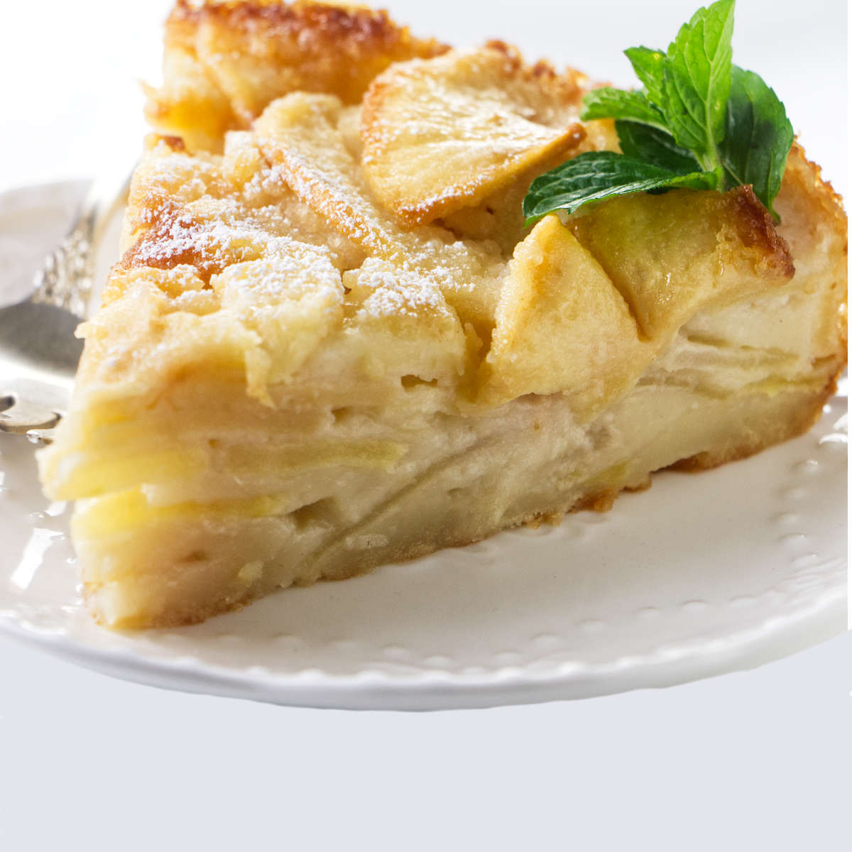 A slice of French apple cake on a dessert plate.