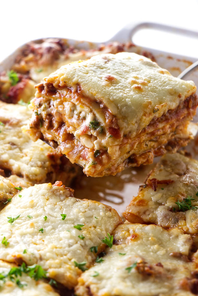 Sausage and beef lasagna being scooped out of a casserole dish.
