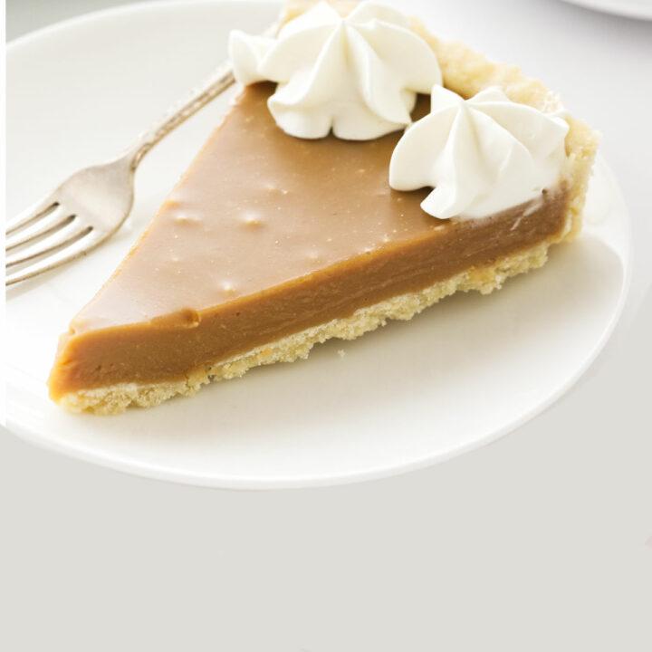 A slice of butterscotch tart on a white dessert plate.