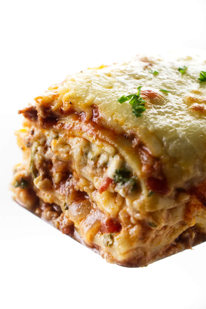 A square slice of lasagna with sausage and beef on a spatula.