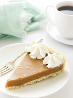 A slice of butterscotch tart with a cup of coffee in the background.