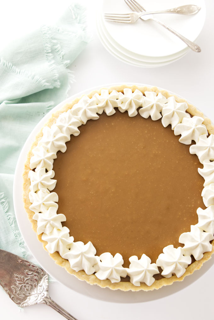 A whole butterscotch tart with whipped cream garnish.
