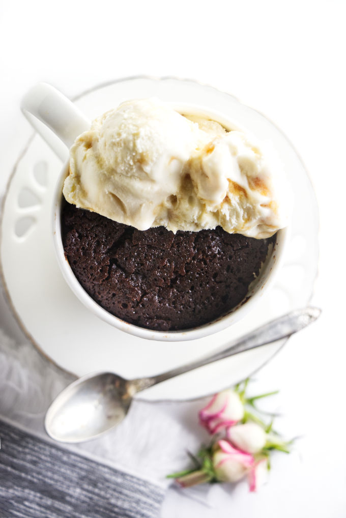 A chocolate mug cake on a saucer with ice cream on top.