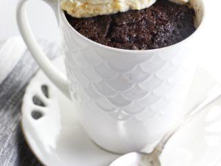A white mug on a saucer with a chocolate cake baked inside the mug.