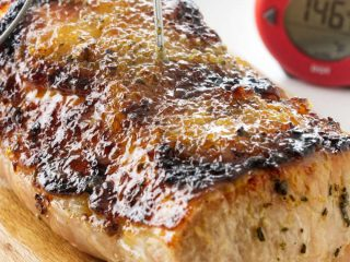 A pork roast with a garlic ginger glaze and a thermometer.