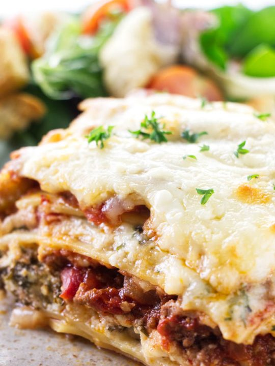 A slice of sausage and beef lasagna on a plate with salad in the background.