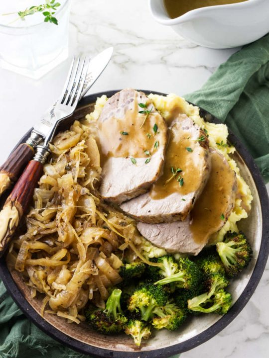 A plate with a serving of pork and sauerkraut with a pitcher of gravy on the side.