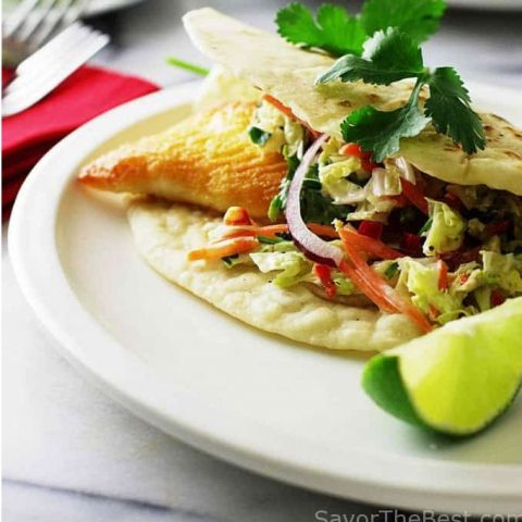 A fish taco on a plate with a slice of lime.