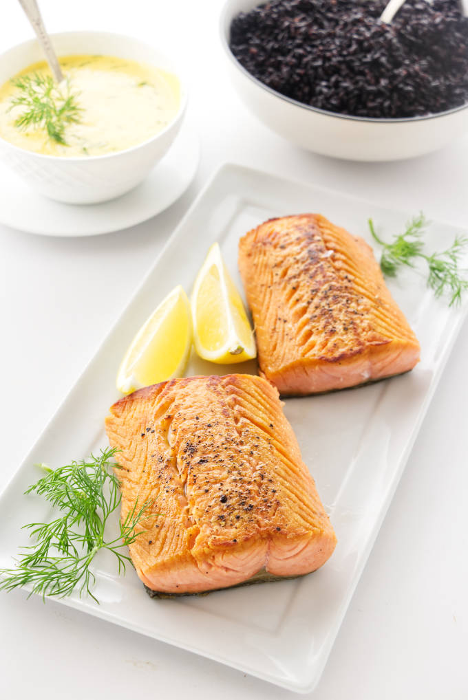 Pan-Seared Salmon with lemon wedges, dish of dill hollandaise sauce and a bowl of black rice in the background