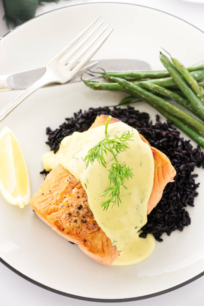 Overhead view of pan seared salmon with dill hollandaise sauce, a sprig of fresh dill