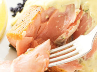 Close up view of a bite of salmon on a fork