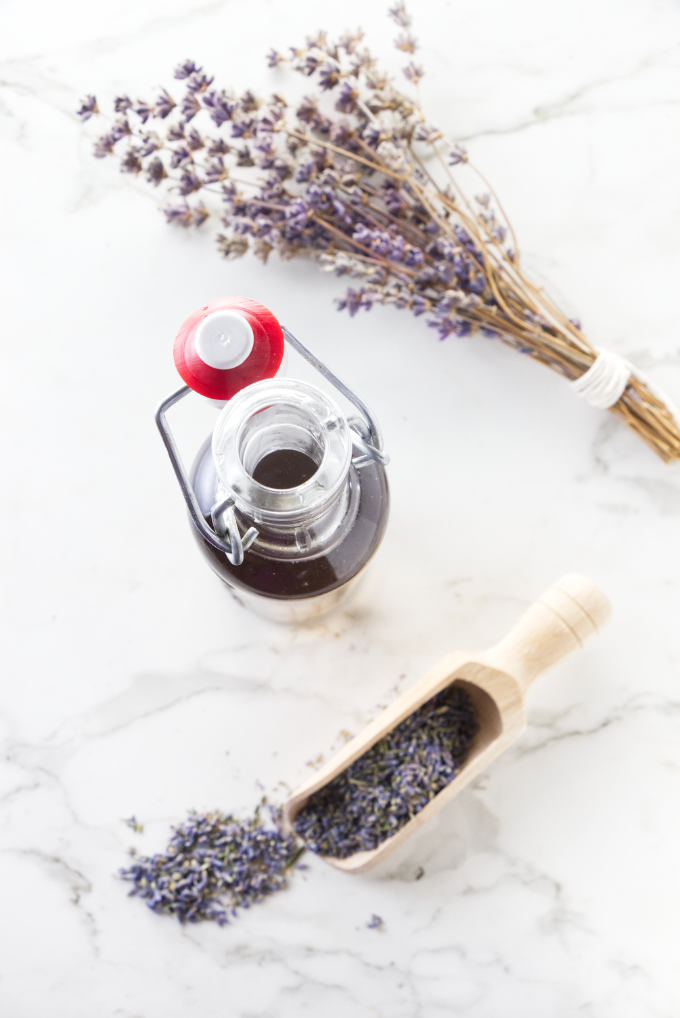 Culinary lavender buds and lavender syrup in a bottle.