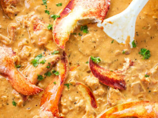Lobster in tomato cream sauce cooking in a skillet.
