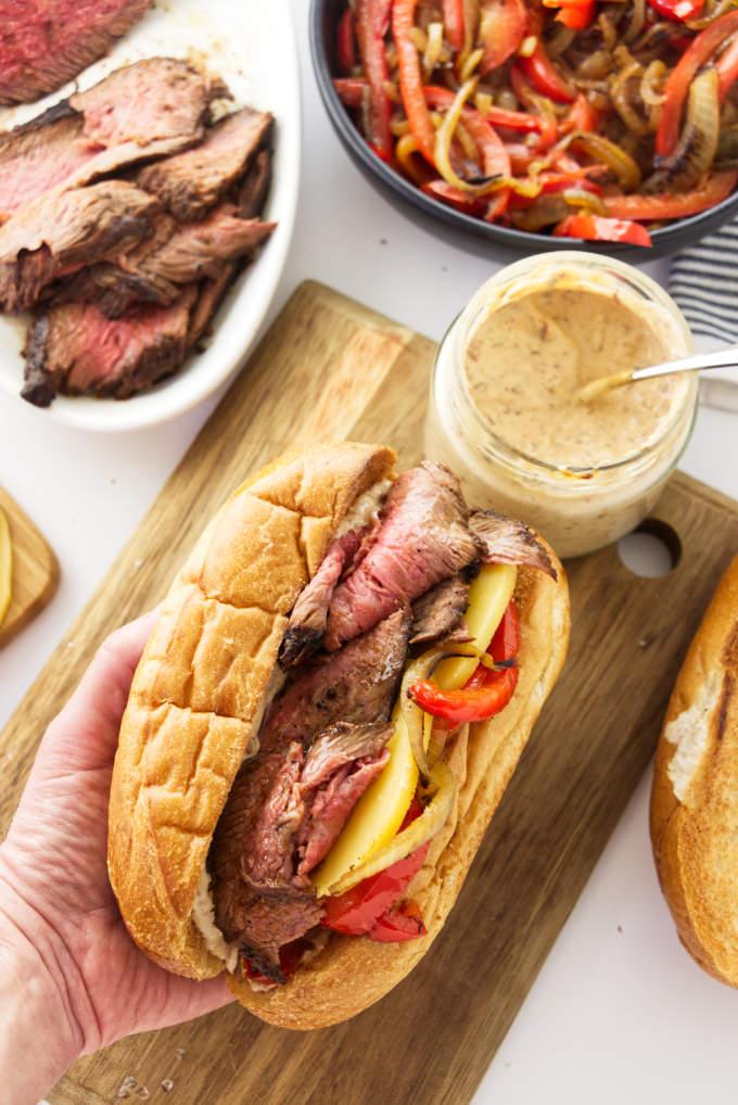 A tri tip sandwich next to a jar of chipotle aioli.