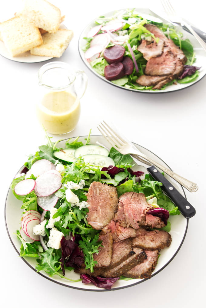 Overhead view of two tri-tip salad servings with dressing on the side