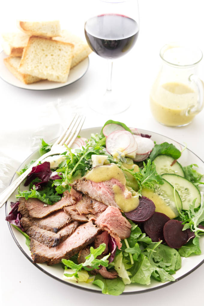 overhead view of a serving of salad, bread, wine and dressing in the background