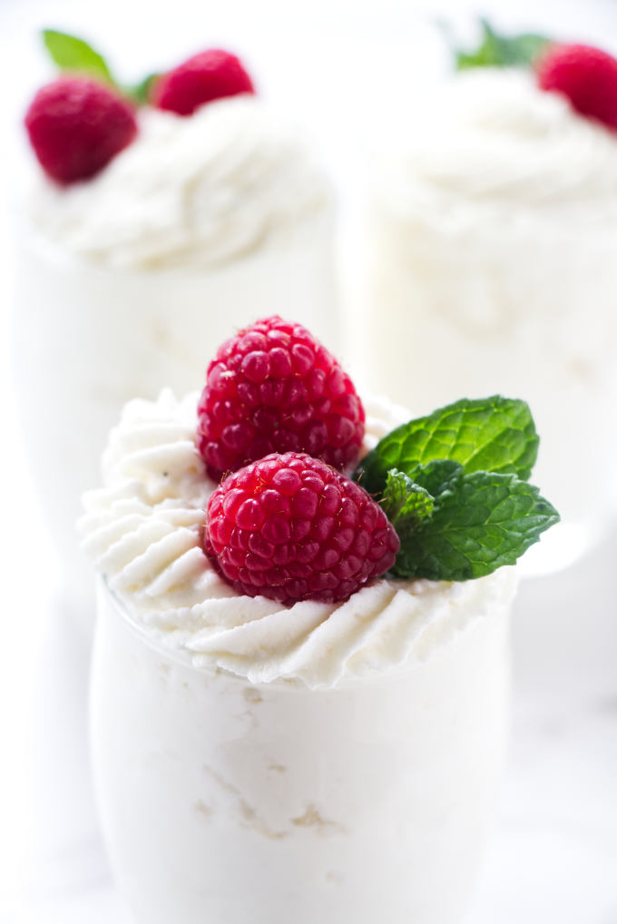 White chocolate mousse for cake being used in dessert cups with fruit on top.