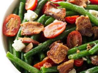 A large bowl of green bean salad with bacon and tomatoes.