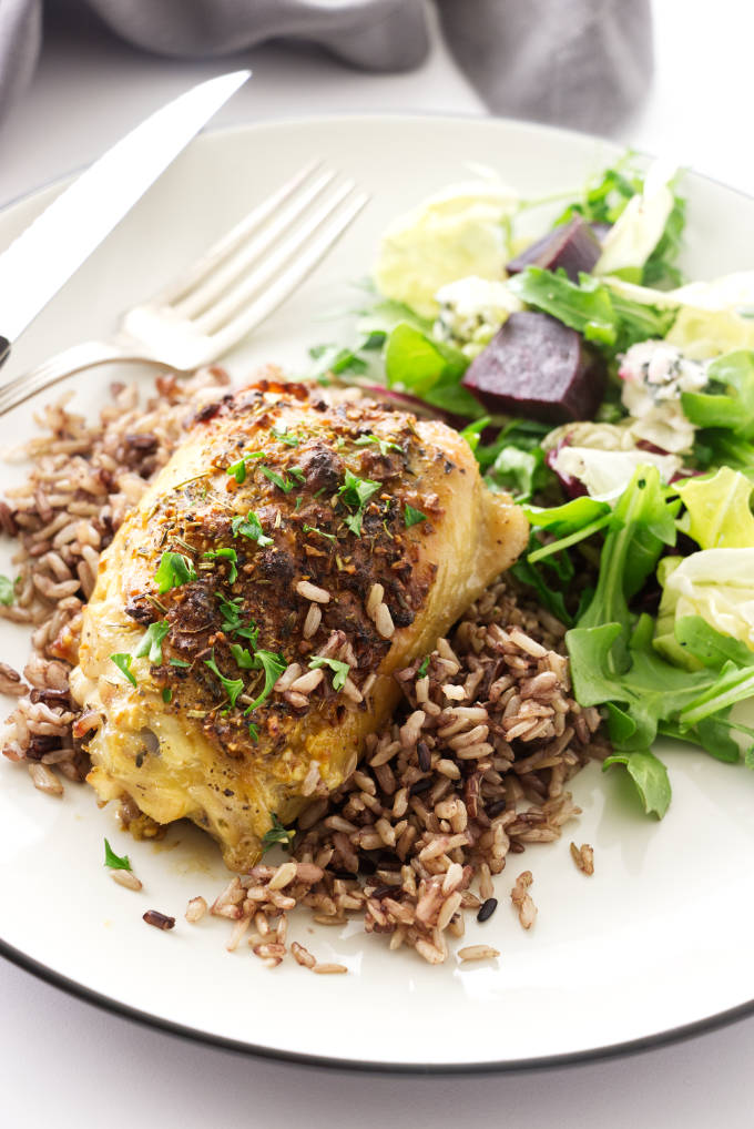 Roasted chicken thigh on a mound of wild blend rice and a side salad