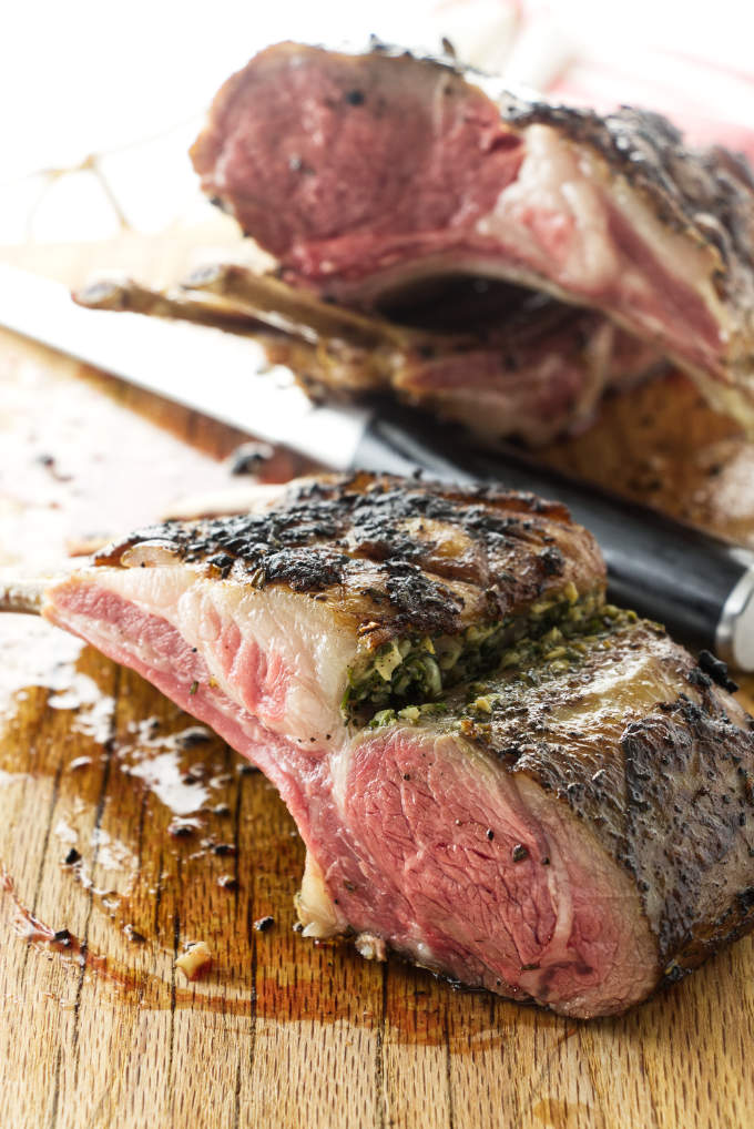 Sous Vide Garlic-Rosemary Rack of Lamb on carving board partially cut into chops