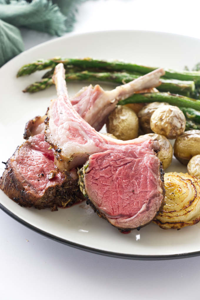 Plated serving of 2 lamb rib chops, with roasted onions, potatoes and asparagus