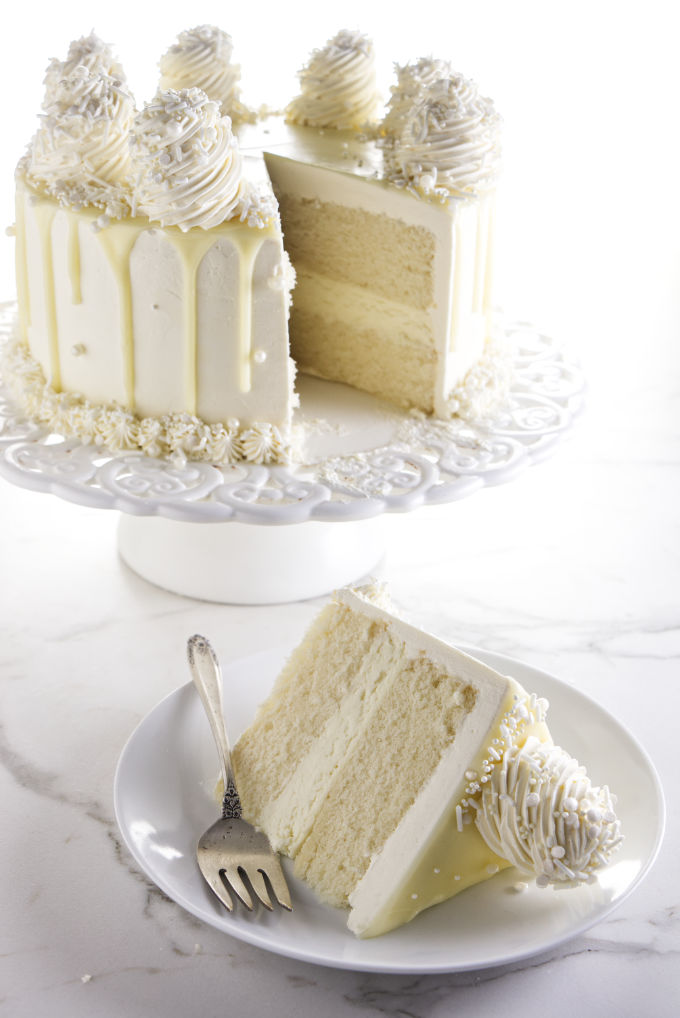 A slice of white chocolate cake on a plate with the larger cake in the background.