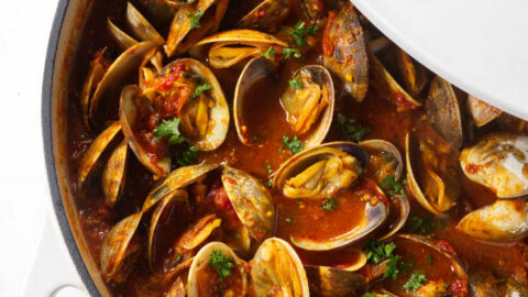 A large pot of clams in red sauce.
