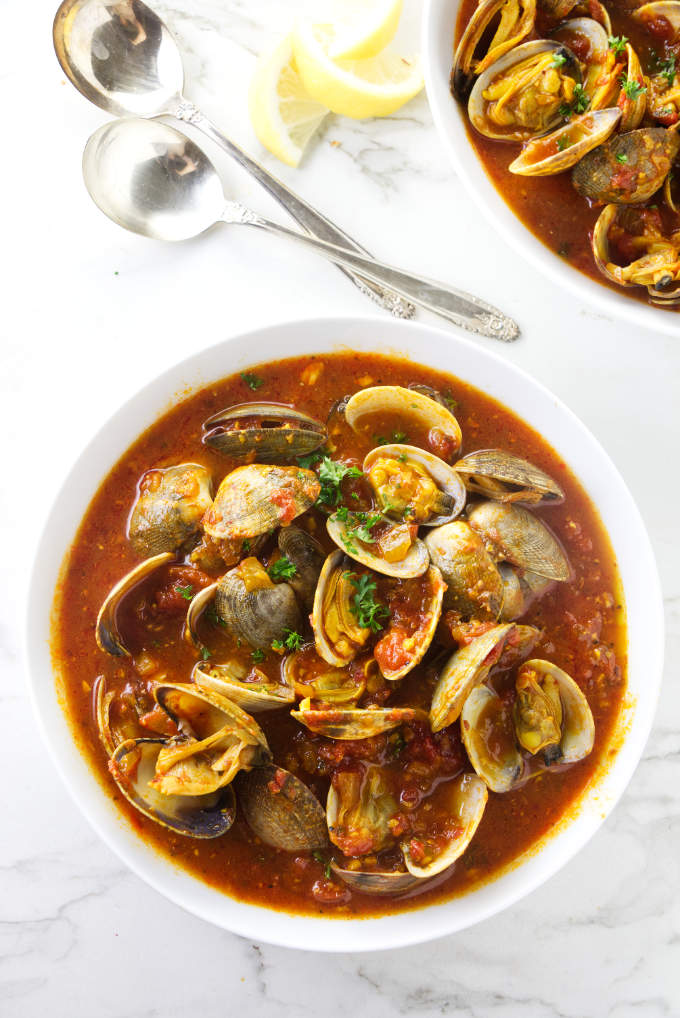 A bowl of clams in red sauce next to some spoons.