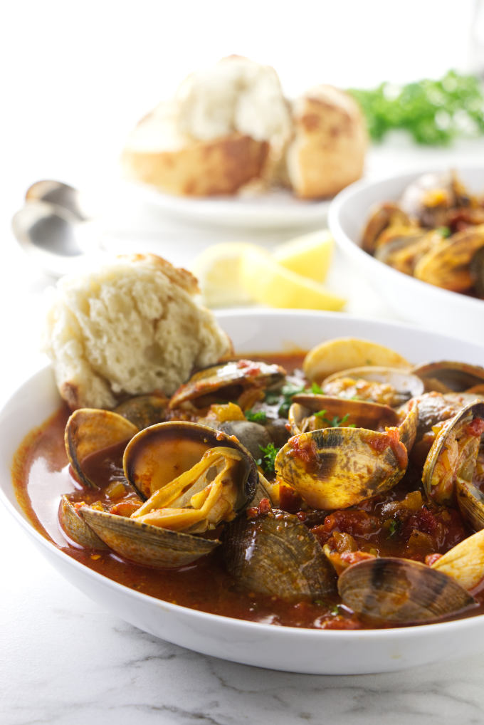 Clams in red sauce in serving bowls.
