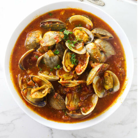 A large bowl of clams in red sauce.