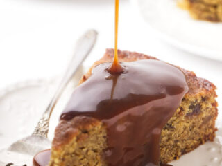 A slice of date cake with sticky toffee sauce being poured on top.