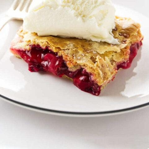 A slice of strawberry rhubarb slab pie with ice cream on top.
